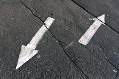 Två pilar på sprucken asfaltyttersida Arkivfoto