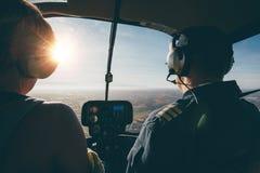 Två piloter i en helikopter, medan flyga på en solig dag Arkivfoton