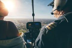 Två piloter som flyger en helikopter på solig dag Fotografering för Bildbyråer