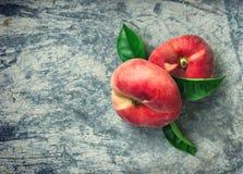 Två plana persikor med sidor Arkivfoton
