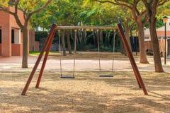 Två platsgungor på barnlekplatsen Royaltyfri Fotografi