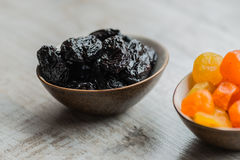 Två plattor med torkade frukter på träbakgrund: torkade mandariner och katrinplommoner Royaltyfri Bild