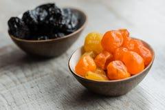 Två plattor med torkade frukter på träbakgrund: torkade mandariner och katrinplommoner Royaltyfria Bilder