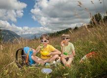 Två pojkar äter på fält i berg arkivfoto