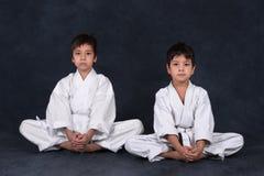 Två pojkar av karatet i en vit kimono arkivbild