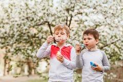 Två pojkar blåser upp såpbubblor i sommaren utomhus royaltyfri foto