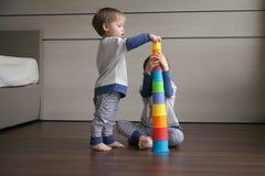 Två pojkar bygger ett torn av ljusa exponeringsglas royaltyfri fotografi