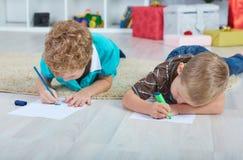 Två pojkar drar Santa Claus på papperet på golvet i barnkammaren royaltyfri foto