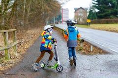 Två pojkar för liten unge, bästa vän som rider på sparkcykeln parkerar in Royaltyfri Foto