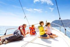 Två pojkar för liten unge, fader och litet barnflicka som tycker om segelbåttur Familjsemestrar p? havet eller havet p? solig dag royaltyfri bild