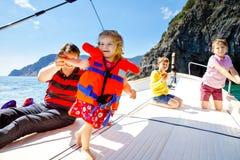 Två pojkar för liten unge, fader och litet barnflicka som tycker om segelbåttur Familjsemestrar p? havet eller havet p? solig dag arkivbilder