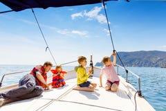 Två pojkar för liten unge, fader och litet barnflicka som tycker om segelbåttur Familjsemestrar p? havet eller havet p? solig dag royaltyfri foto
