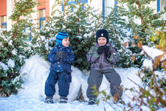Två pojkar för liten unge i färgrik kläder som utomhus spelar under snöfall Aktiv fritid med barn i vinter på kalla dagar slump Royaltyfria Bilder