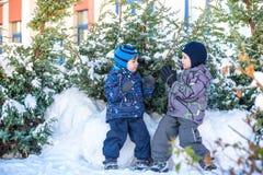 Två pojkar för liten unge i färgrik kläder som utomhus spelar under snöfall Aktiv fritid med barn i vinter på kalla dagar slump Arkivfoto