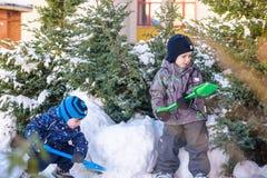 Två pojkar för liten unge i färgrik kläder som utomhus spelar under snöfall Aktiv fritid med barn i vinter på kalla dagar slump Arkivfoton