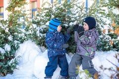 Två pojkar för liten unge i färgrik kläder som utomhus spelar under snöfall Aktiv fritid med barn i vinter på kalla dagar slump Royaltyfri Fotografi