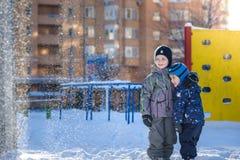 Två pojkar för liten unge i färgrik kläder som utomhus spelar under snöfall Aktiv fritid med barn i vinter på kalla dagar slump Arkivbild