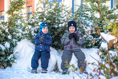 Två pojkar för liten unge i färgrik kläder som utomhus spelar under snöfall Aktiv fritid med barn i vinter på kalla dagar slump Royaltyfria Foton