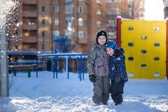 Två pojkar för liten unge i färgrik kläder som utomhus spelar under snöfall Aktiv fritid med barn i vinter på kalla dagar slump Arkivbilder