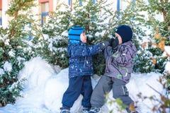 Två pojkar för liten unge i färgrik kläder som utomhus spelar under snöfall Aktiv fritid med barn i vinter på kalla dagar slump Fotografering för Bildbyråer