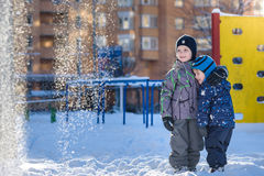 Två pojkar för liten unge i färgrik kläder som utomhus spelar under snöfall Aktiv fritid med barn i vinter på kalla dagar slump Royaltyfri Bild