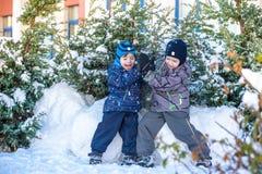 Två pojkar för liten unge i färgrik kläder som utomhus spelar under snöfall Aktiv fritid med barn i vinter på kalla dagar slump Royaltyfri Foto
