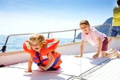 Två pojkar för liten unge och litet barnflicka som tycker om segelbåttur Familjsemestrar p? havet eller havet p? solig dag Barn royaltyfri foto