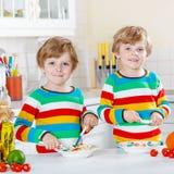 Två pojkar för liten unge som äter spagetti i hemhjälp Arkivfoto
