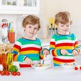 Två pojkar för liten unge som äter spagetti i hemhjälp Arkivbild