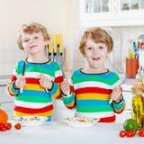Två pojkar för liten unge som äter spagetti i hemhjälp Arkivfoton