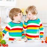 Två pojkar för liten unge som äter spagetti i hemhjälp Arkivbilder
