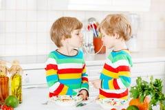 Två pojkar för liten unge som äter spagetti i hemhjälp Royaltyfria Bilder