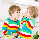 Två pojkar för liten unge som äter spagetti i hemhjälp Royaltyfri Fotografi