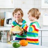 Två pojkar för liten unge som äter spagetti i inhemskt kök Fotografering för Bildbyråer