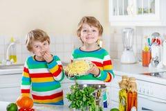 Två pojkar för liten unge som äter spagetti i inhemskt kök Arkivbild