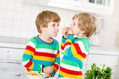 Två pojkar för liten unge som äter spagetti i inhemskt kök Royaltyfria Bilder