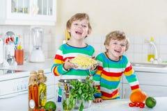 Två pojkar för liten unge som äter spagetti i inhemskt kök Royaltyfri Foto