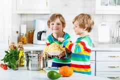 Två pojkar för liten unge som äter spagetti i inhemskt kök Arkivfoton