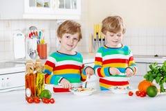 Två pojkar för liten unge som äter spagetti i inhemskt kök Royaltyfria Foton
