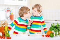Två pojkar för liten unge som äter spagetti i inhemskt kök Arkivbilder