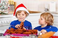 Två pojkar för liten unge som bakar pepparkakakakor Arkivfoto