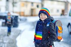 Två pojkar för små ungar av elementär grupp som går till skolan under snöfall Lyckliga barn som har roligt och spelar med arkivbilder