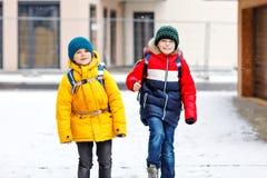 Två pojkar för små ungar av elementär grupp som går till skolan under snöfall Lyckliga barn som har roligt och spelar med royaltyfri fotografi