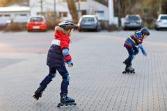 Två pojkar för små ungar som åker skridskor med rullar i staden Lyckliga barn, syskon och bästa vän i skyddssäkerhet arkivbild