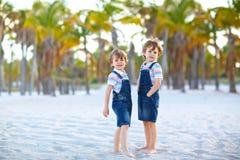 Två pojkar för små ungar som har gyckel på den tropiska stranden, lyckliga bästa vän som spelar, kamratskapbegrepp Syskonbröder arkivbilder
