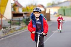 Två pojkar för små ungar som rider på pushsparkcyklar på vägen till eller från skolan Skolpojkar av 7 år som kör till och med reg royaltyfri fotografi