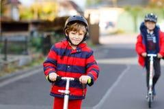 Två pojkar för små ungar som rider på pushsparkcyklar på vägen till eller från skolan Skolpojkar av 7 år som kör till och med reg royaltyfria bilder