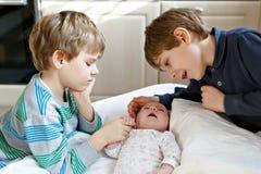 Två pojkar för små ungar som spelar med nyfött, behandla som ett barn systerflickan fotografering för bildbyråer