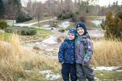 Två pojkar för små ungar, vänner som rymmer händer och att krama Förtjusande syskon i ljus färgrik kläder Lyckliga barn utomhus,  fotografering för bildbyråer