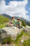 Två pojkar har fått picknicken i berg Royaltyfri Foto